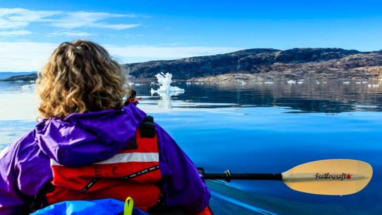 Up close of a female kayaker pausing to admire the landscape of greenland with calm waters, blue skies, and icebergs passing by