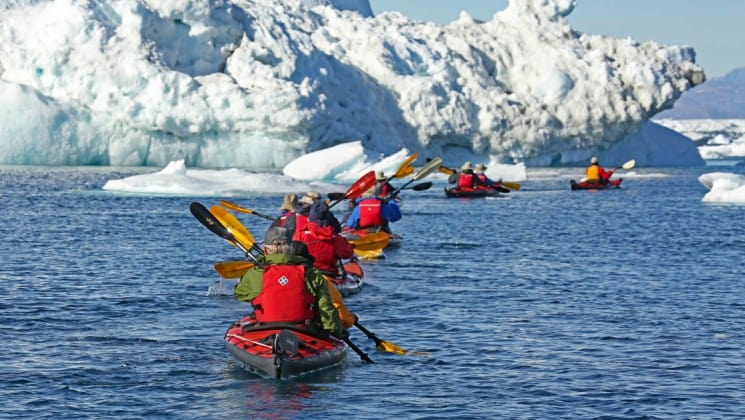 group of small ship cruise passengers on a kayak excursion and following their guide going past icebergs in Greenland
