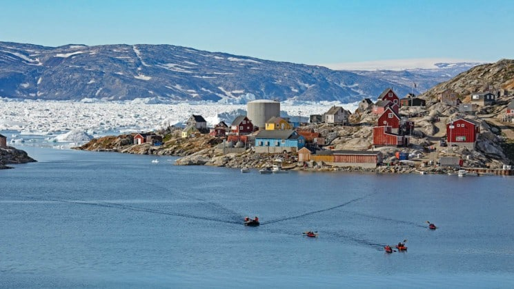 Four kayakers and a skiff paddling back from a small village in Greenland with ice pack in the distance