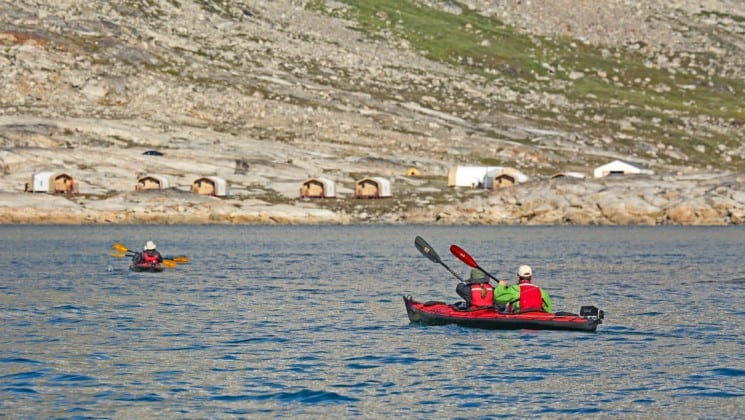 Two kayakers paddling towards land in Greenland with local camps on the rocky terrain