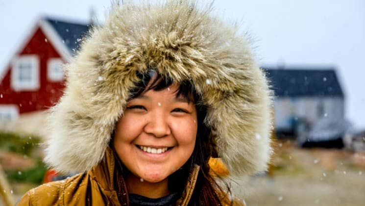 local greenlandic inuit woman smiling with a fur hat and snow falling
