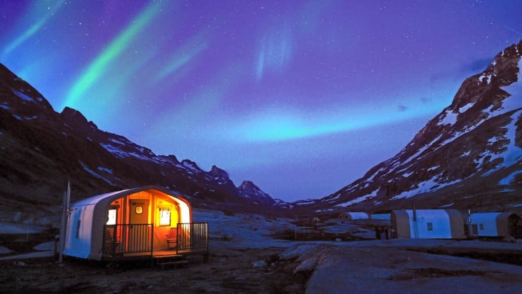 Basecamp hut lit up at night with the northern lights above and mountain peaks on both sides