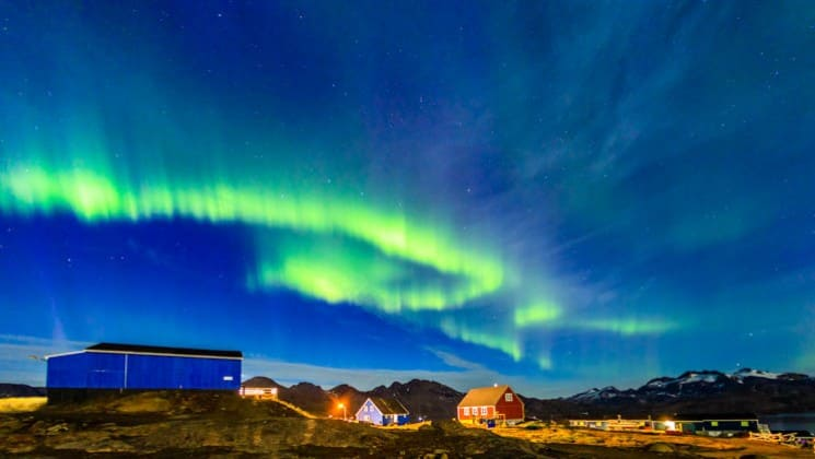 Green flash of the northern lights seen in a dark blue sky above a small village in greenland