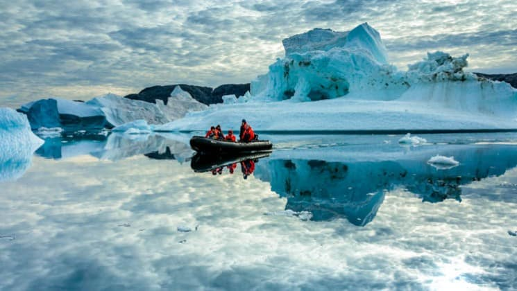 Skiff excursion with group surrounded by uniquely shaped icebergs and reflections on the still water