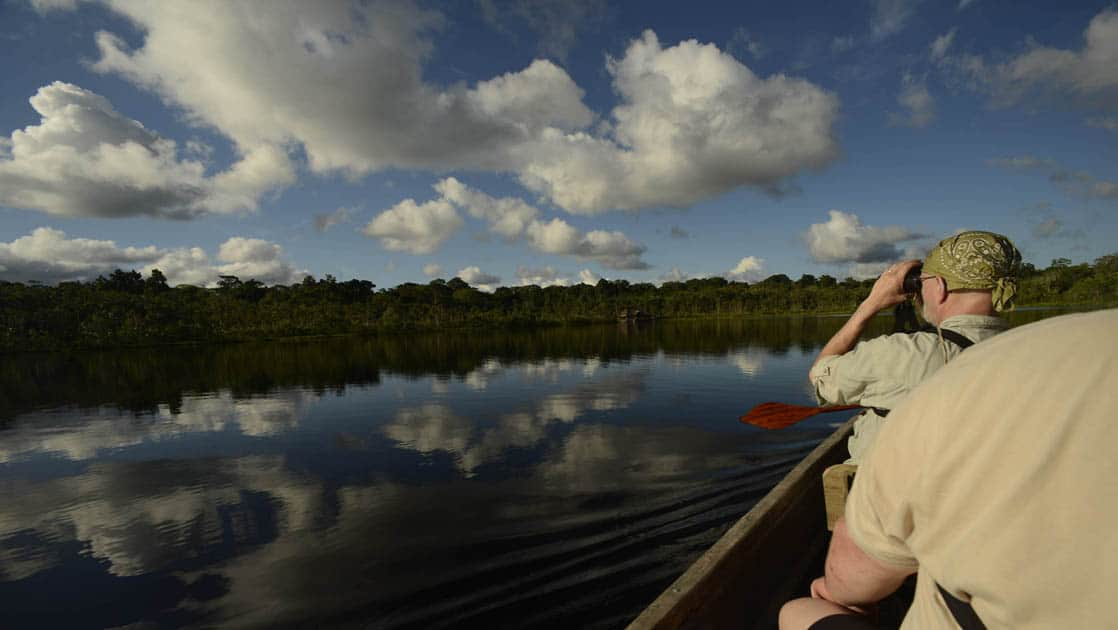 amazon travelers taking pictures from a small boat with the jungle in the distance on a sunny day with clouds above