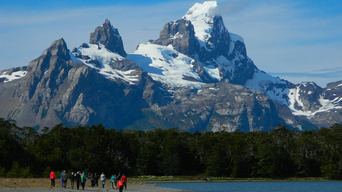 adventure travelers trek across land toward jagged patagonia mountains in the distance