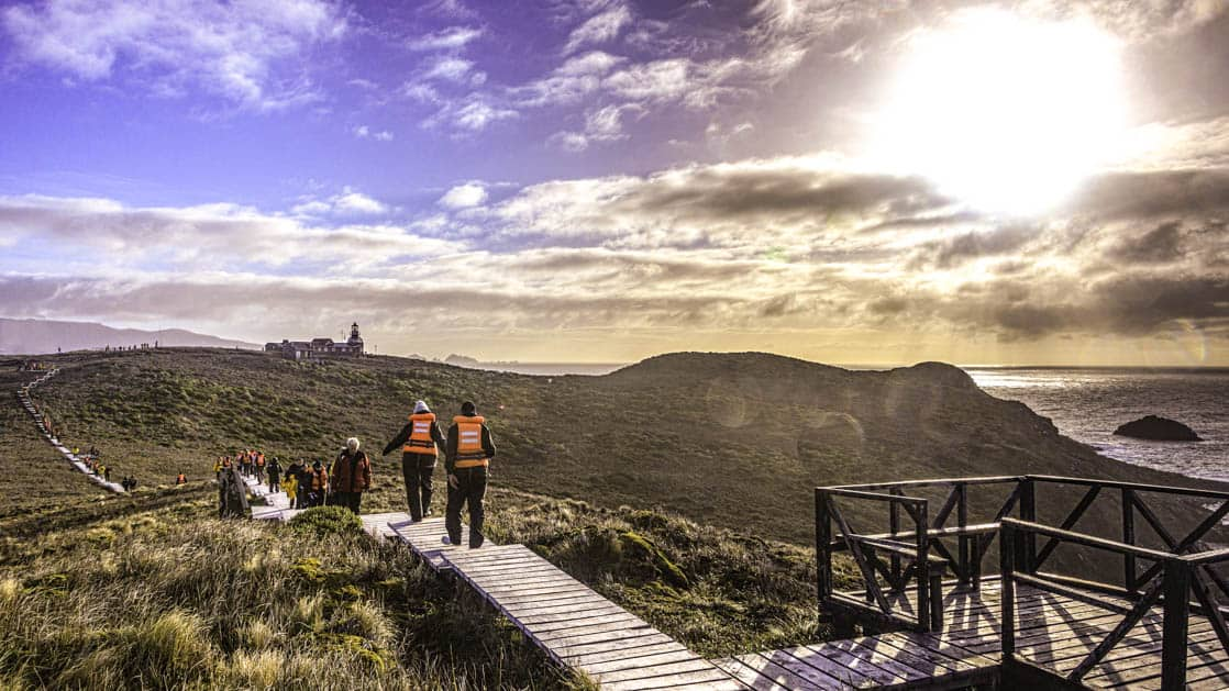 group of travelers walk down a wooden path with grass on all sides toward a building in the distance that is sitting on a ridge overlooking the ocean in patagonia