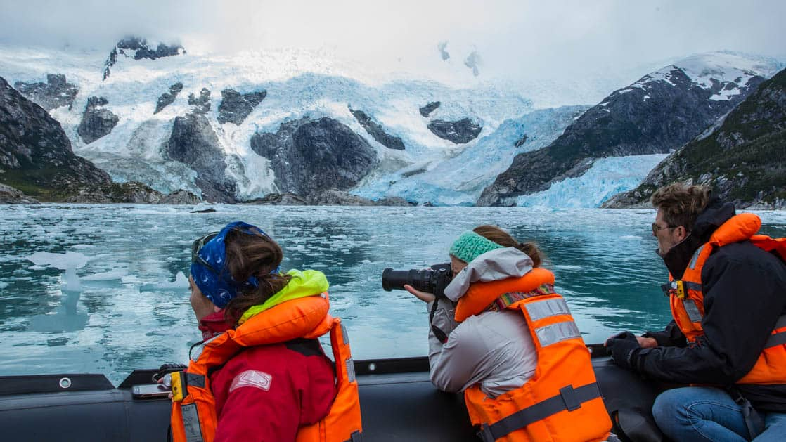 adventure travelers sitting on the edge of a small ship taking pictures across the water of patagonia fjords