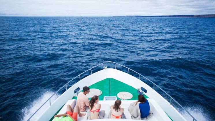 galapagos adventure travelers sitting on the bow of a small ship with blue sea in front of them