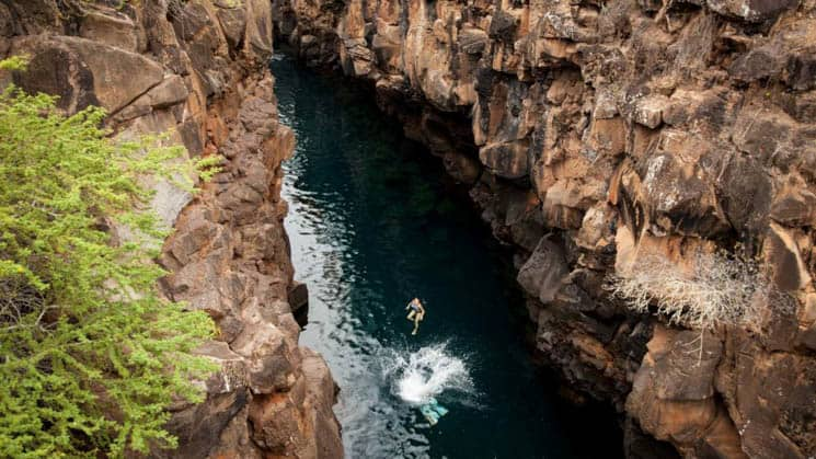 solo traveler on the galapagos discovery land tour in mid air between 2 cliffs above a narrow strip of water