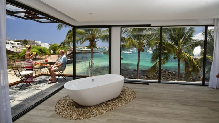 standalone bathtub on wood floor of a luxury galapagos hotel with large windows behind it overlooking the ocean and travelers sitting outside