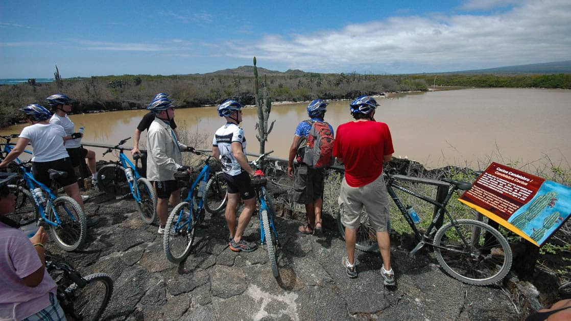 group of adventure travelers on the galapagos island hopper trip with mountain bikes parked overlooking water and jungle
