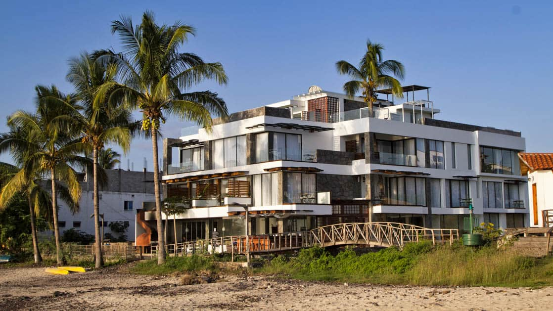 white multilayered luxury galapagos hotel with palm trees around it on a sunny day