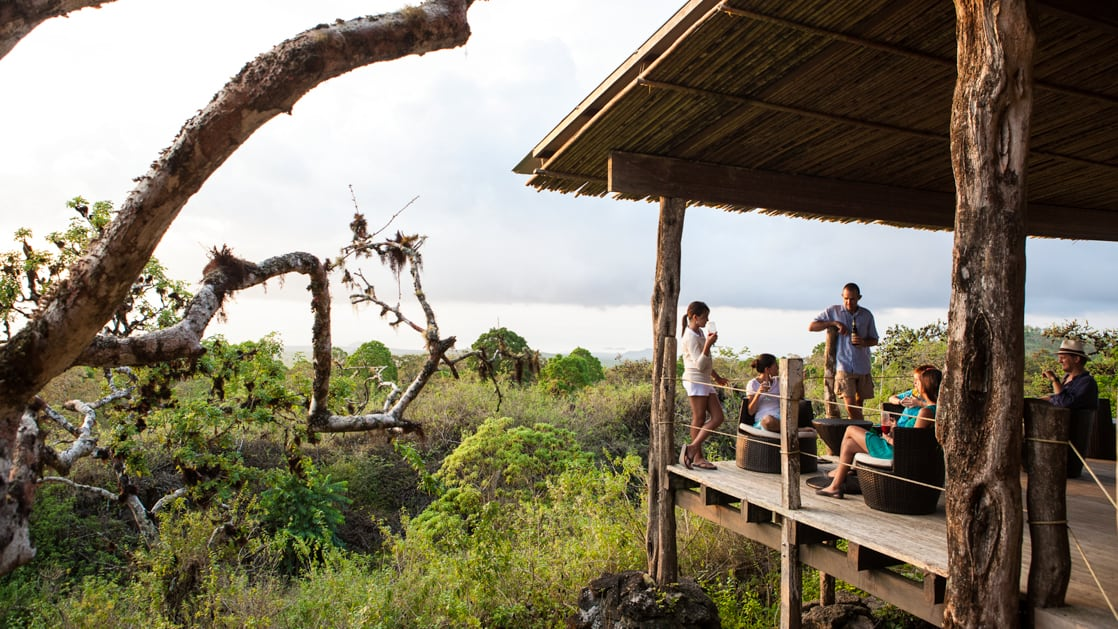 family of travelers sits on the balcony of their bungalow overlooking the ocean with trees below them at galapagos safari camp