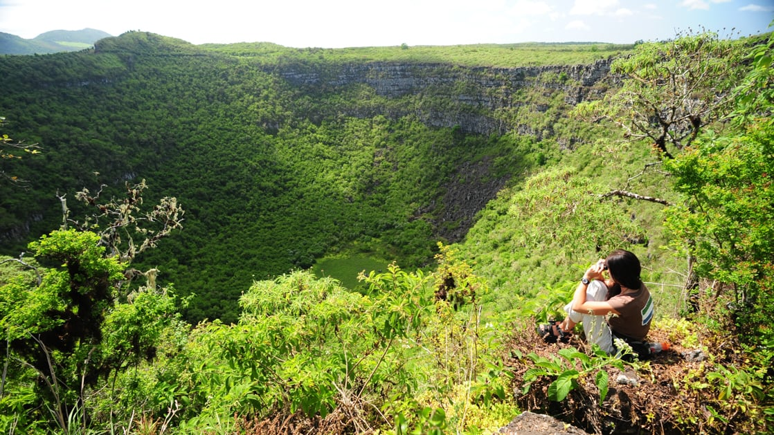 female solo traveler sits on the edge of a lush green galapagos valley and takes a picture