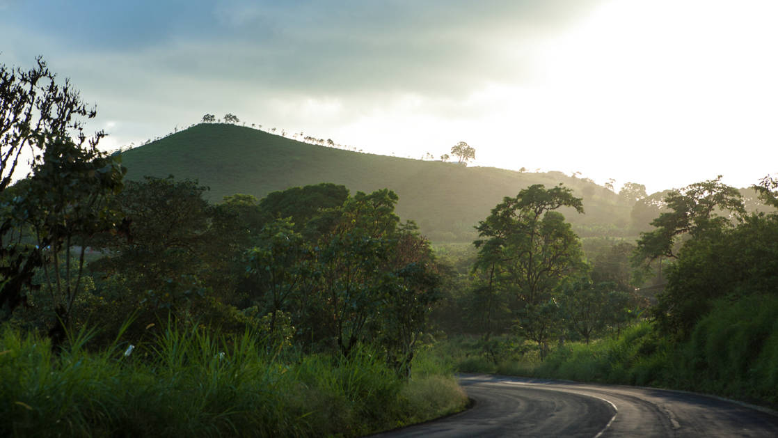 view of a mountain with a road leading toward it during the morning at galapagos safari camp