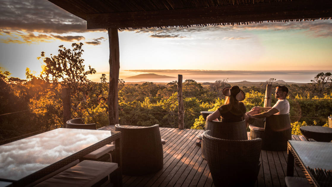 adventure travelers sit on the deck of their bungalow at galapagos safari camp looking out over the jungle and ocean as the sun sets in the distance