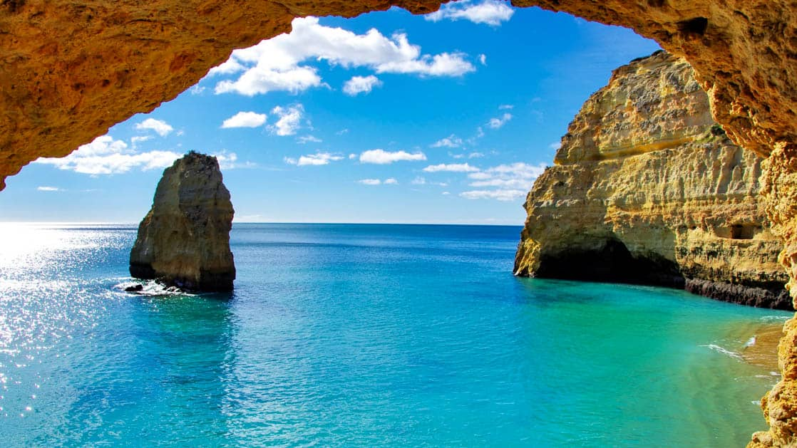 rock formations in the bright blue water on the algarve coast in portugal