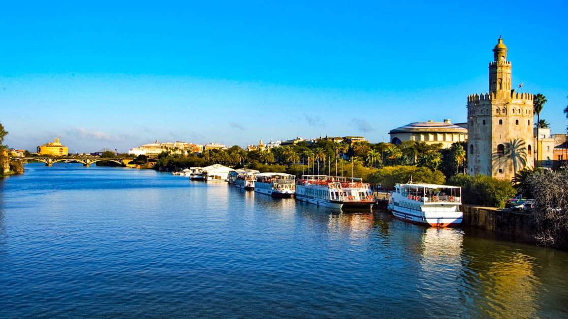 Boats along the promenade of the seville river in spain with a bridge in the background