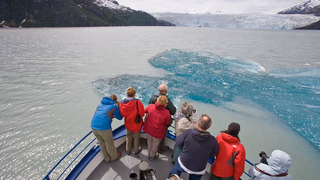 Passengers on the bow of the MV Discovery looking down at the ice in the water as they approach a glacier in prince william sound alaska