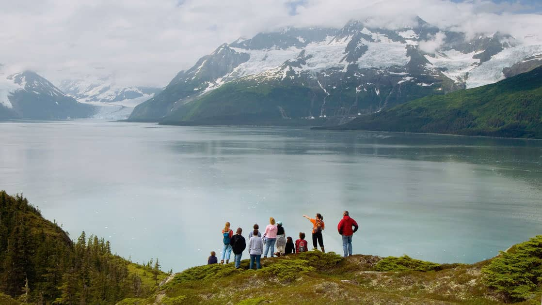 Hikers admiring the view of a glacier in the distance in alaska