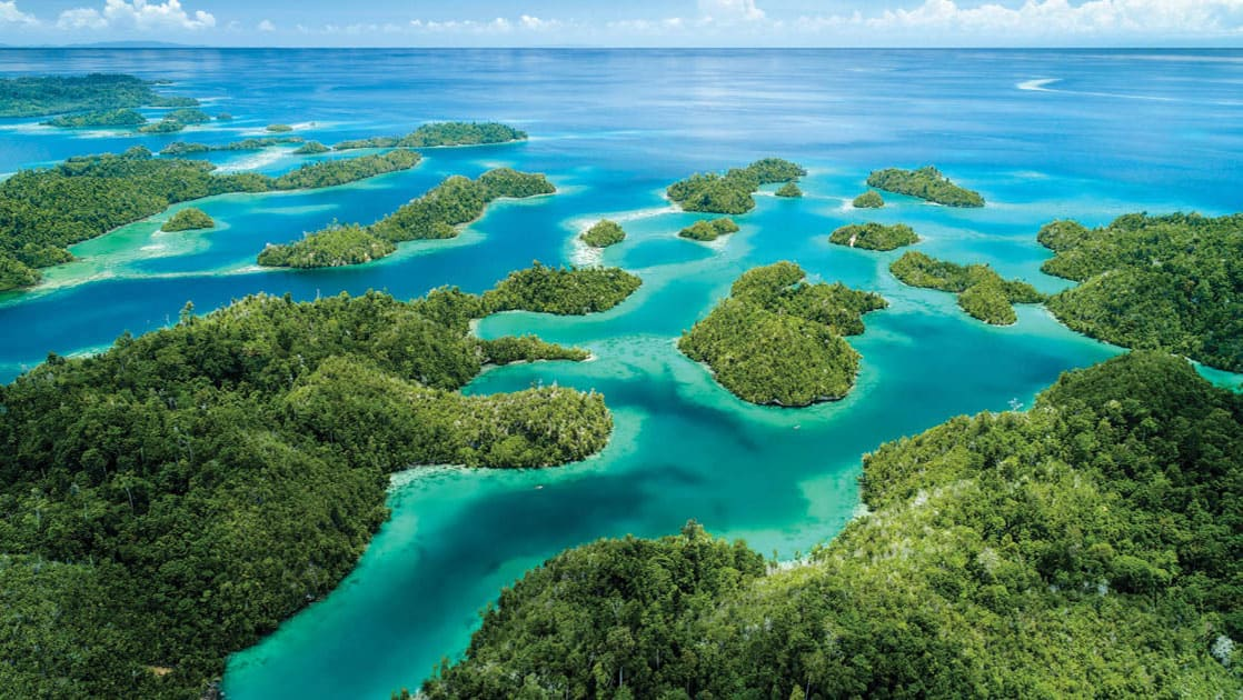 looking down the many of islands of indonesia with turquoise and aqua colored ocean in between