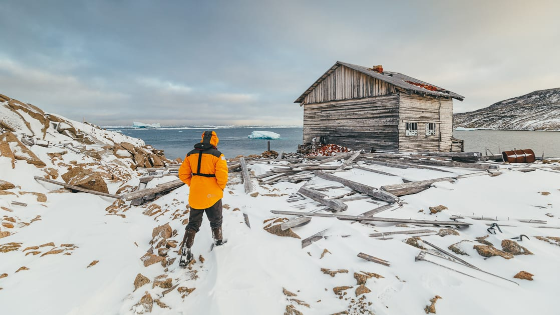 Polar traveler in yellow jacket walks over snowy ground toward an old wooden hut during the Jewels of the Russian Arctic small ship cruise.