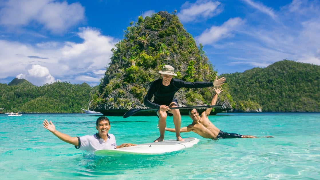 three travelers playing on a stand up paddleboard in crystalline water with vibrant green islands behind them on a sunny day in indonesia