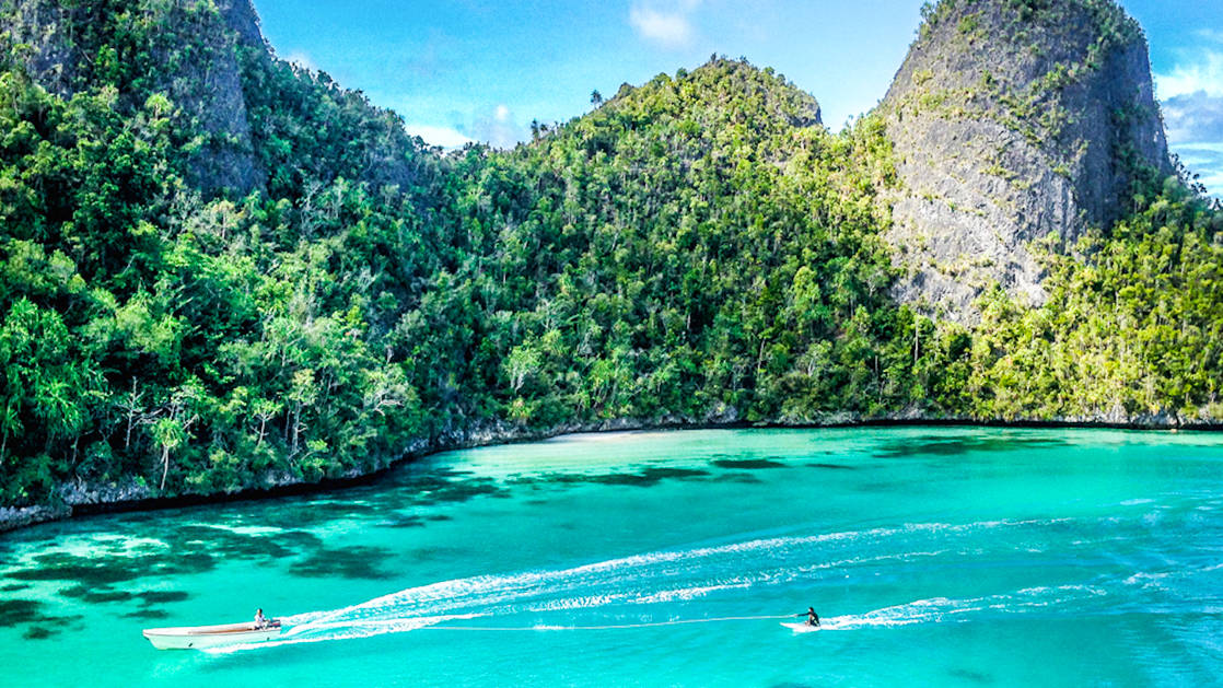 gorgeous turquoise cove surrounded by jungle in indonesia with a small ship pulling a traveler on a stand up paddleboard