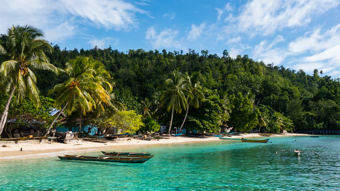 a small indonesia beach with blue buildings behind the trees, white sand and small boats floating in turquoise water with jungle and palm trees surrounding it