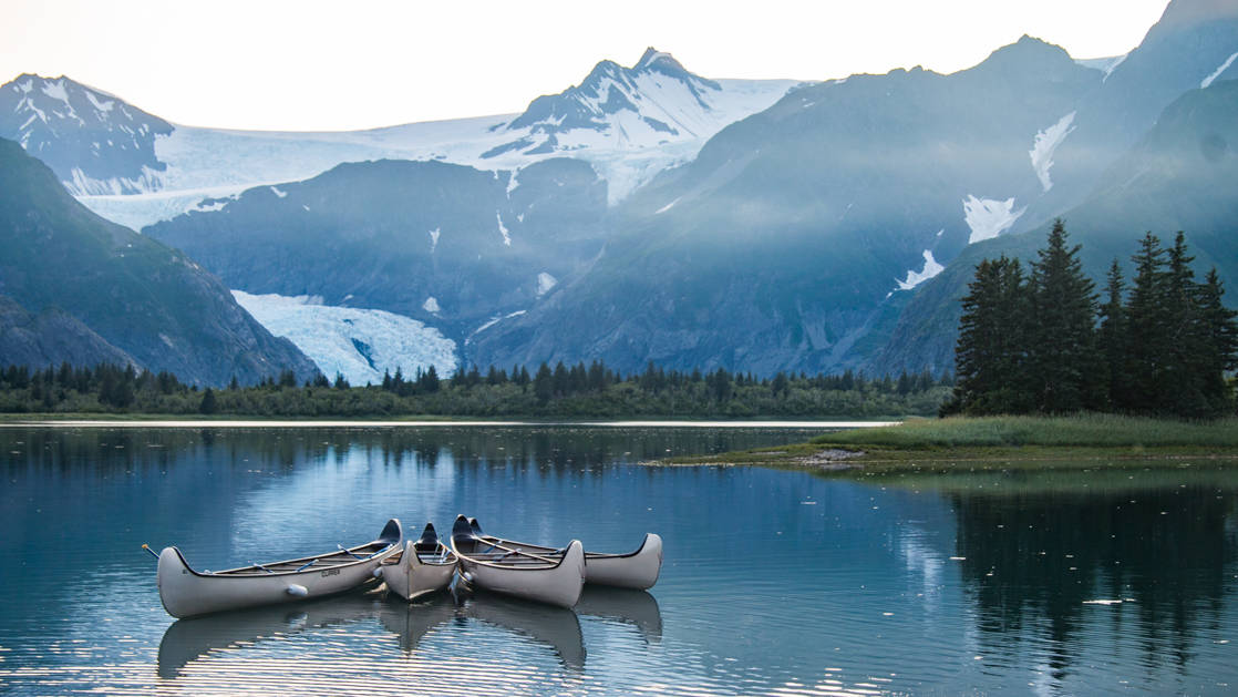 Three canoes across the water from a glacier in kenai fjords alaska