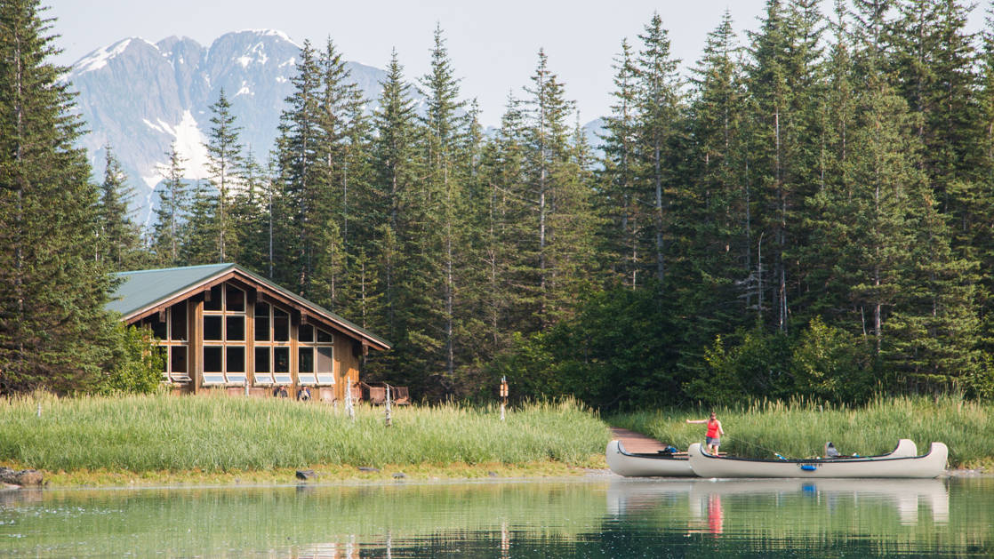 Kenai fjords glacier lodge near water with two canoes, a forest, and mountains behind.