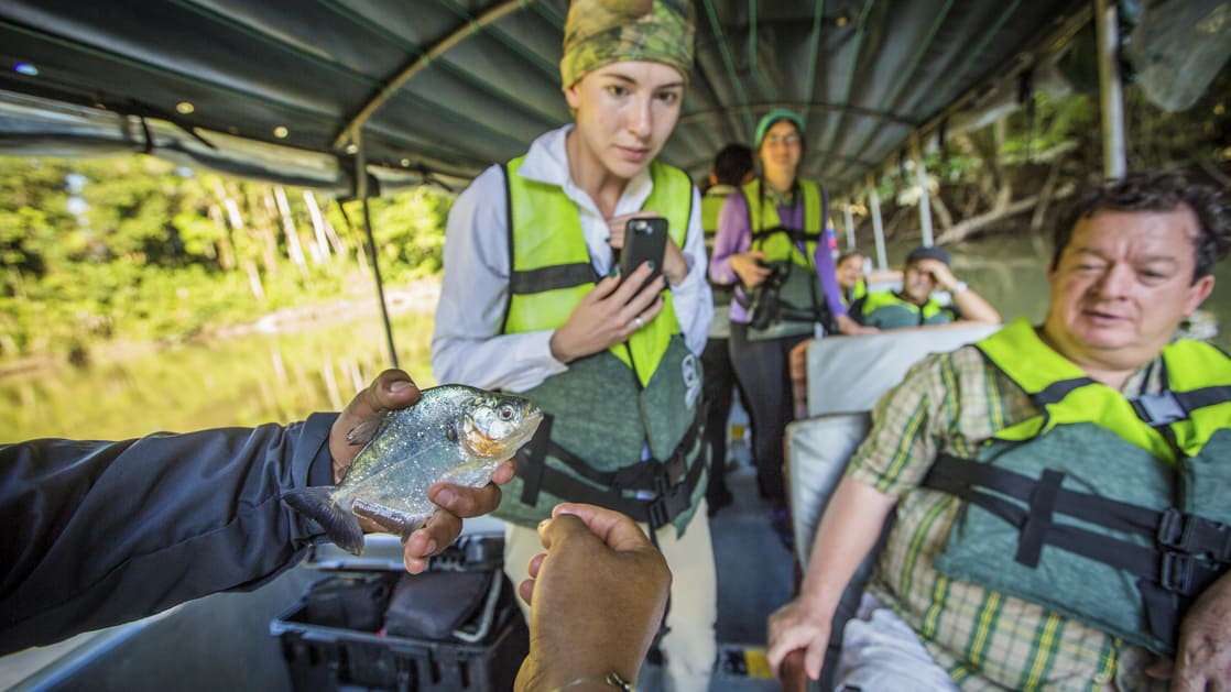 guide holding a fish in his hand to show to the group of passengers on a boat excursion in the amazon