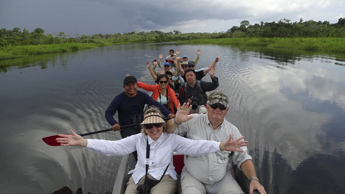 group of small ship passengers on a canoe excursion and raising their arms in excitement to pose for a pictures in the amazon