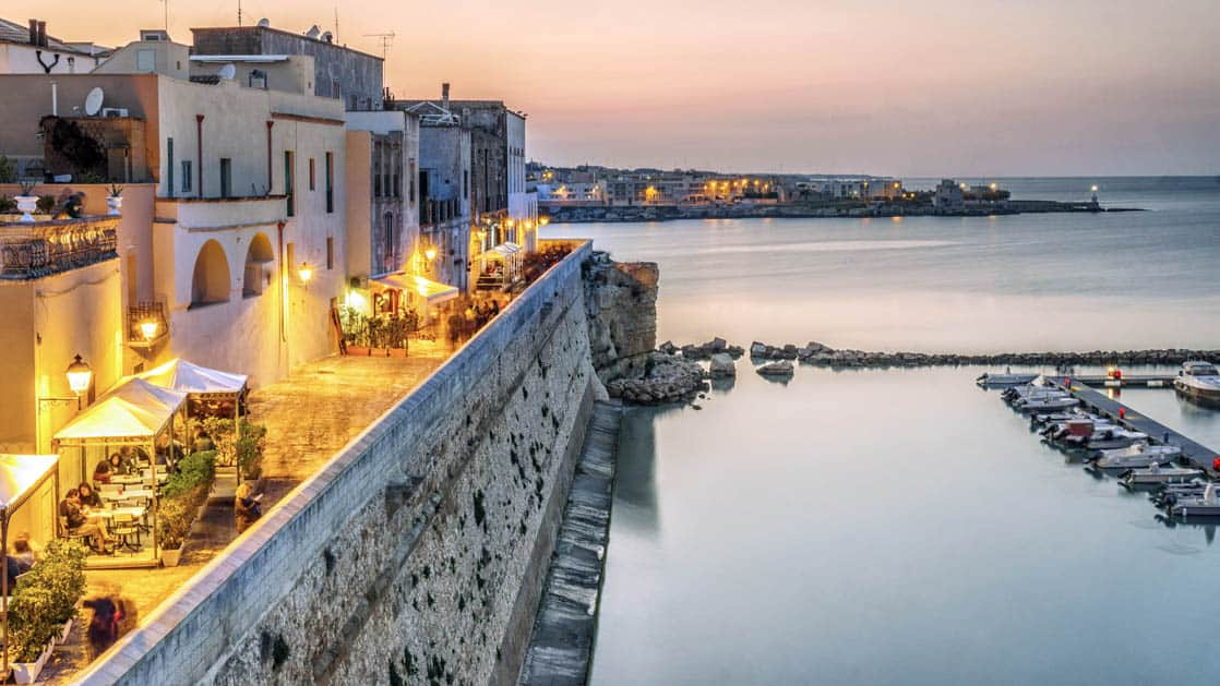 Beautiful Otranto with restaurants lit up at night by the Adriatic Sea in Puglia, Italy