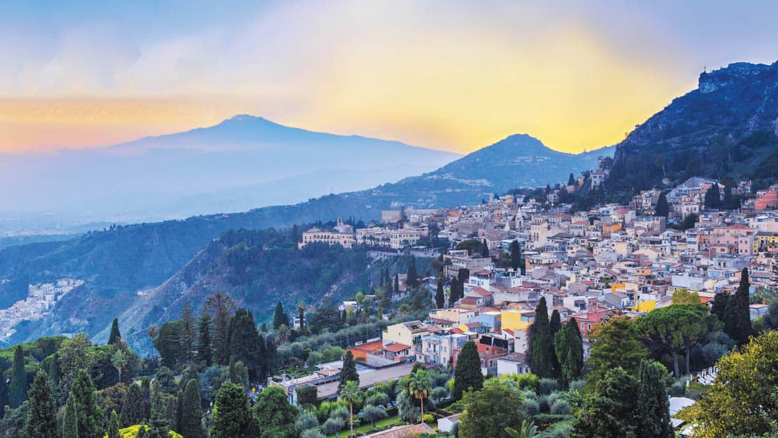The italian village of taormina on the hills of sicily with many trees at sunset