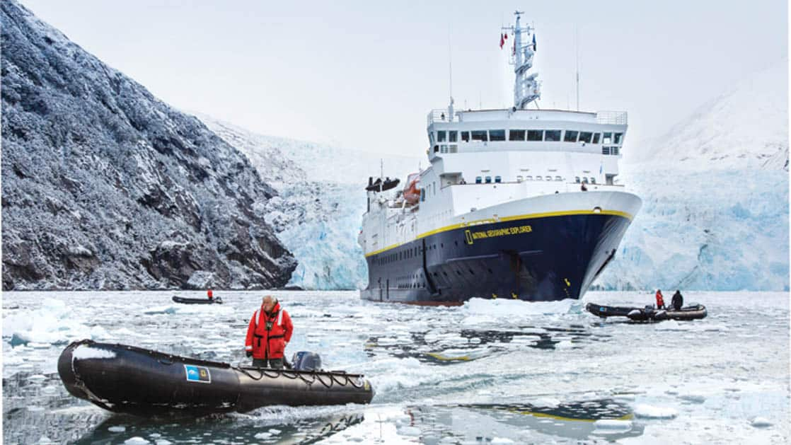 National Geographic small ship in front of glacier and two skiffs in front surrounded by ice in Garibaldi Fjord of Tierra Del Fuego Patagonia
