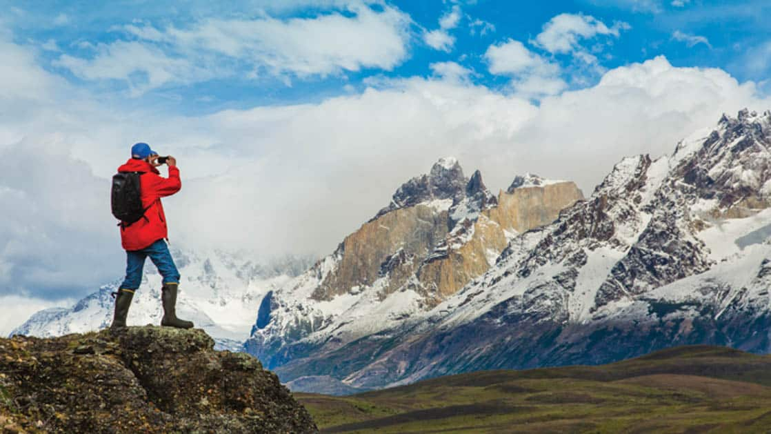 Hiker standing on rock and taking Photos of the snowy and jagged mountain landscape in Torres Del Paine National Park, Patagonia