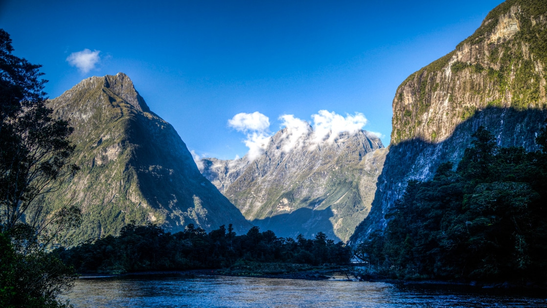 Coastal mountain rangesseen from a small expedition ship in New Zealand on a sunny day.