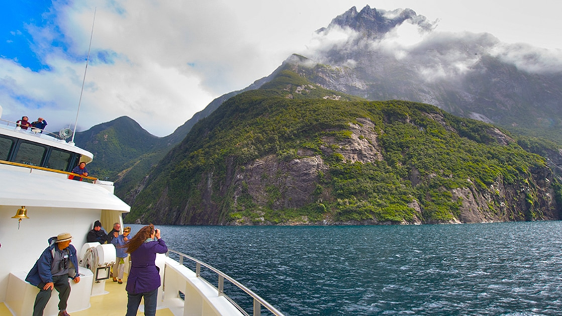 Several expedition cruise guests on the bow of their ship in New Zealand photographing the tall green coastal mountains with their peaks in the clouds.