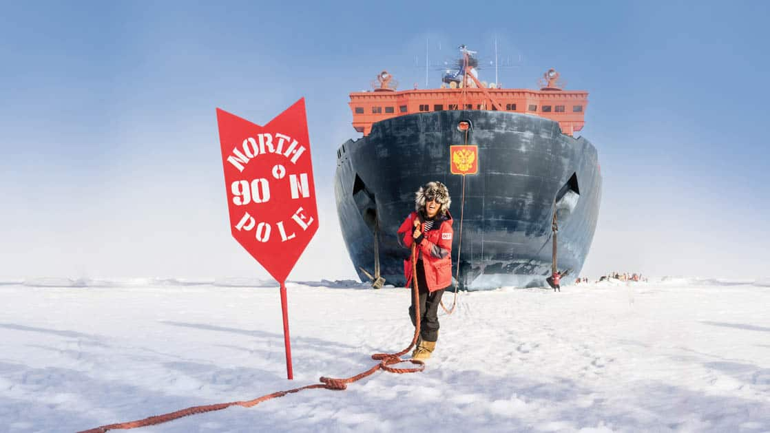 A person in a parka holds a rope and pretends to pull the fifty years of victory ship to the north pole