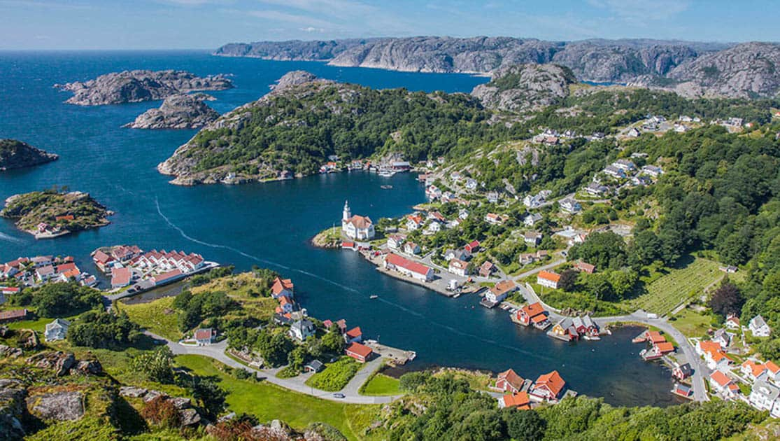 View of Hidra Norway from above, with many red roof houses amongst the green trees and hills and little rocky islands in the water