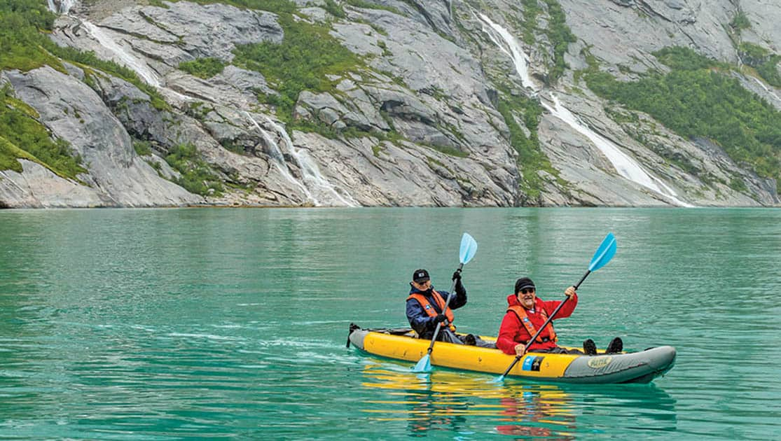 Tandem kayak paddling in the green waters of the Norwegian Fjords, close to the cliffs and waterfalls