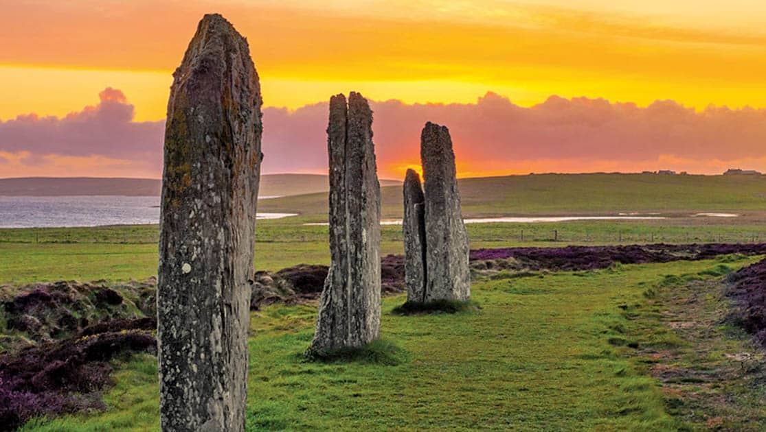 Three standing stones of the ancient and mysterious Ring of Brodgar underneath a dramatic sunset in Scotland