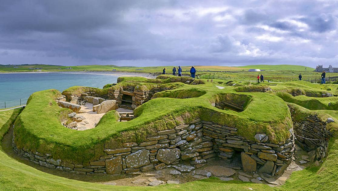 Several people walking around the stone ruins in the green grass at Skara Brae in Orkney Scotland