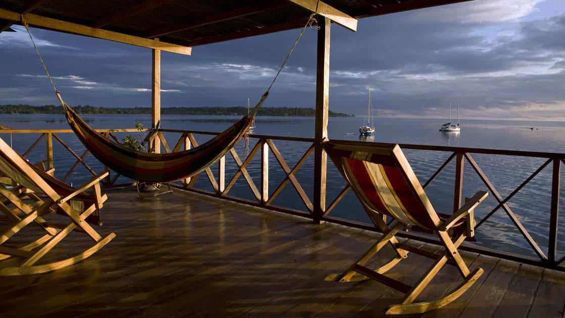 A hammock and rocking chairs on the deck of Bocas Del Toro lodge in Panama as the sun sets.