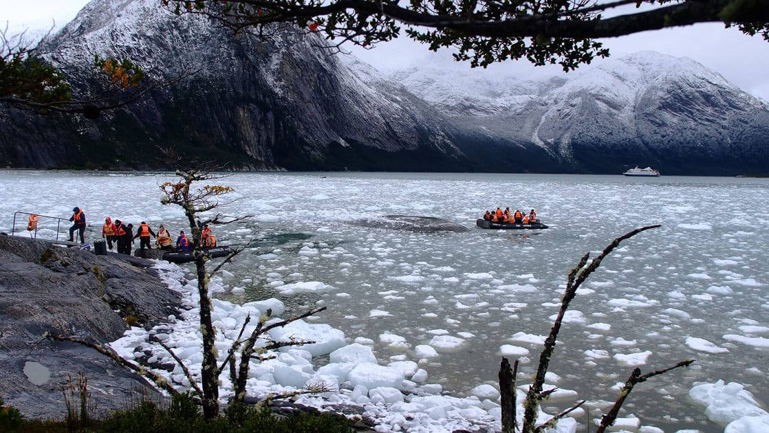 travelers load into and ride in zodiac skiffs on icy water with a small cruise ship anchored in the distance on an overcast day in patagonia