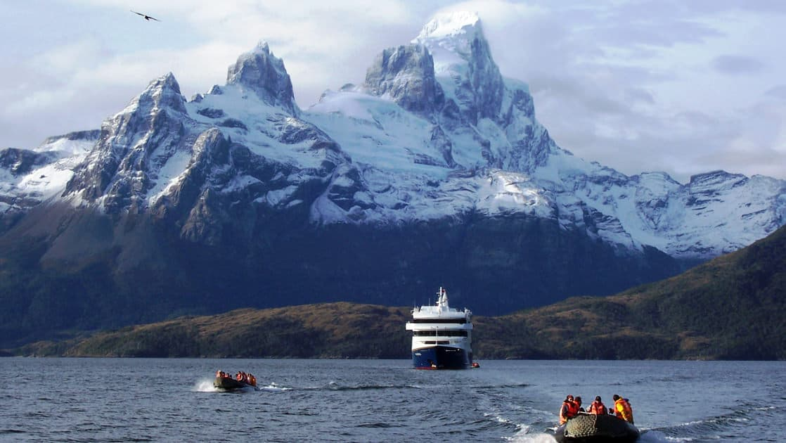 travelers ride away from a small cruise ship on a partly cloudy day in patagonia with large mountains covered in snow jut out in the distance