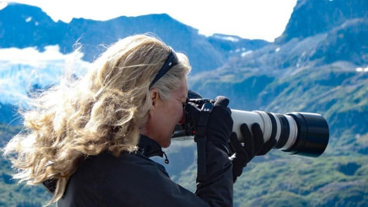 female solo traveler taking a photo with a long lens into the wilderness in alaska on a sunny day