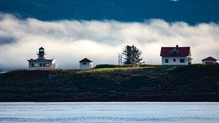 small seaside town on a grassy knoll overlooks the water with mist behind them on a sunny day in alaska